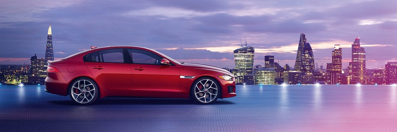 Red Jaguar XE next to London skyline at dusk